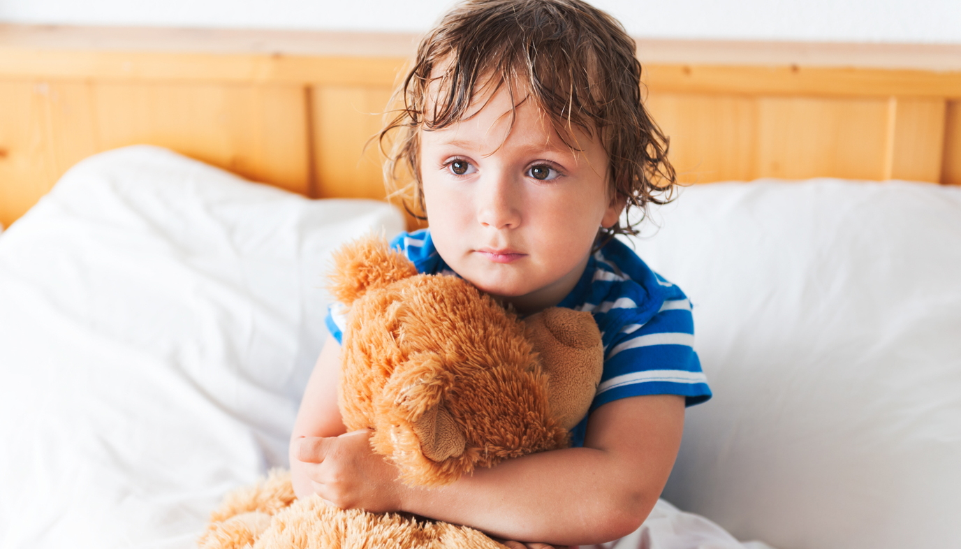 child holding teddy bear in bed