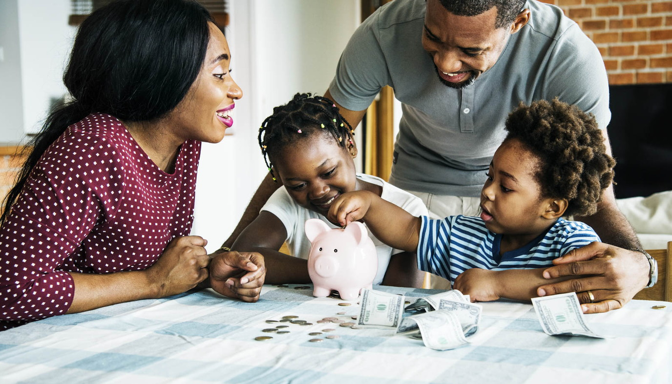 family putting money into a piggy bank