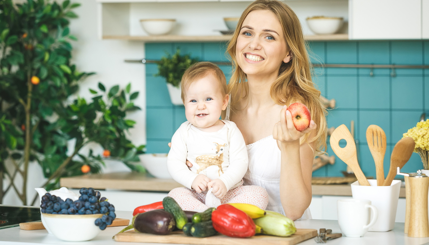 woman preparing vegetables with baby