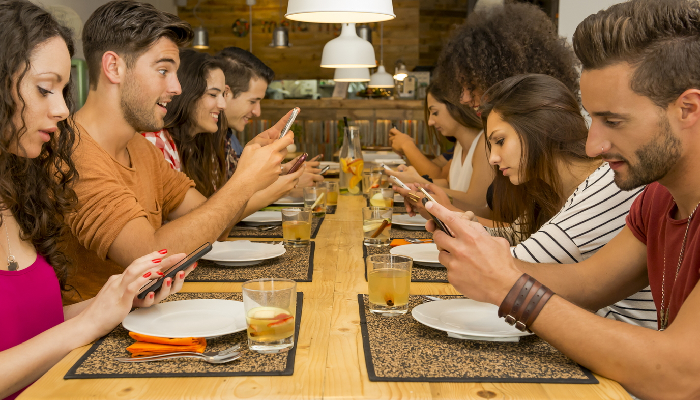 family at table using their cell phones