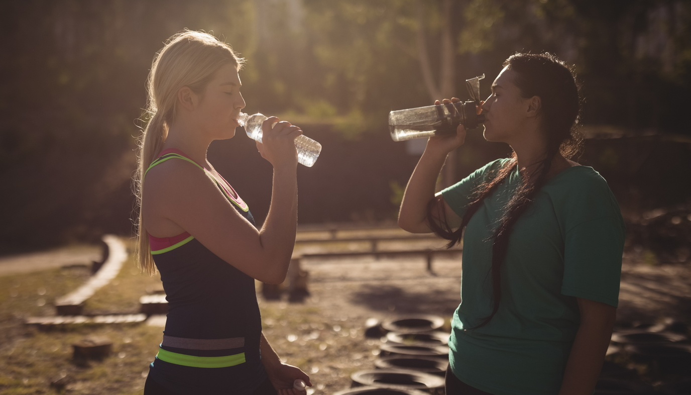 women drinking water after workout
