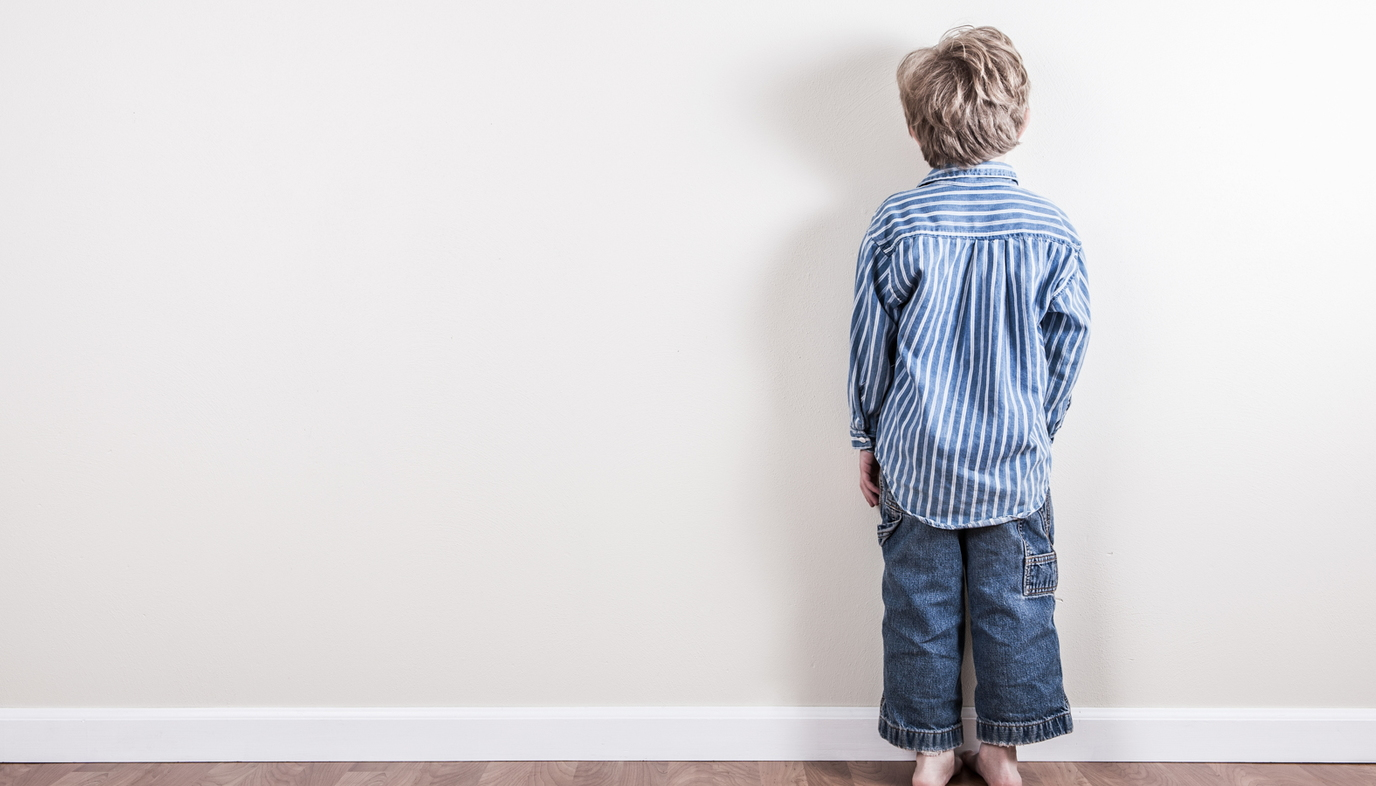 boy standing against the wall