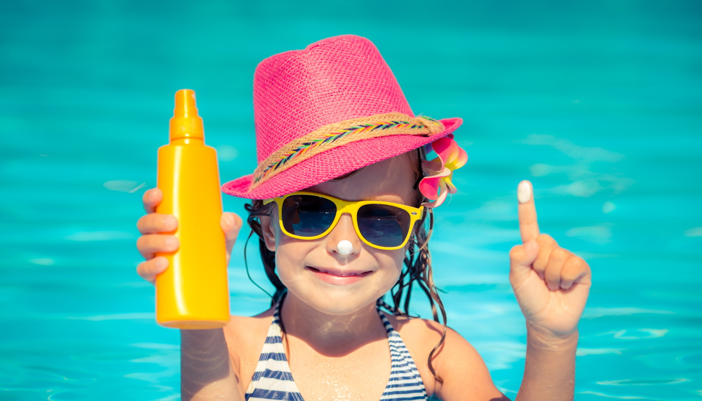 girl in the pool holding bottle of sunscreen