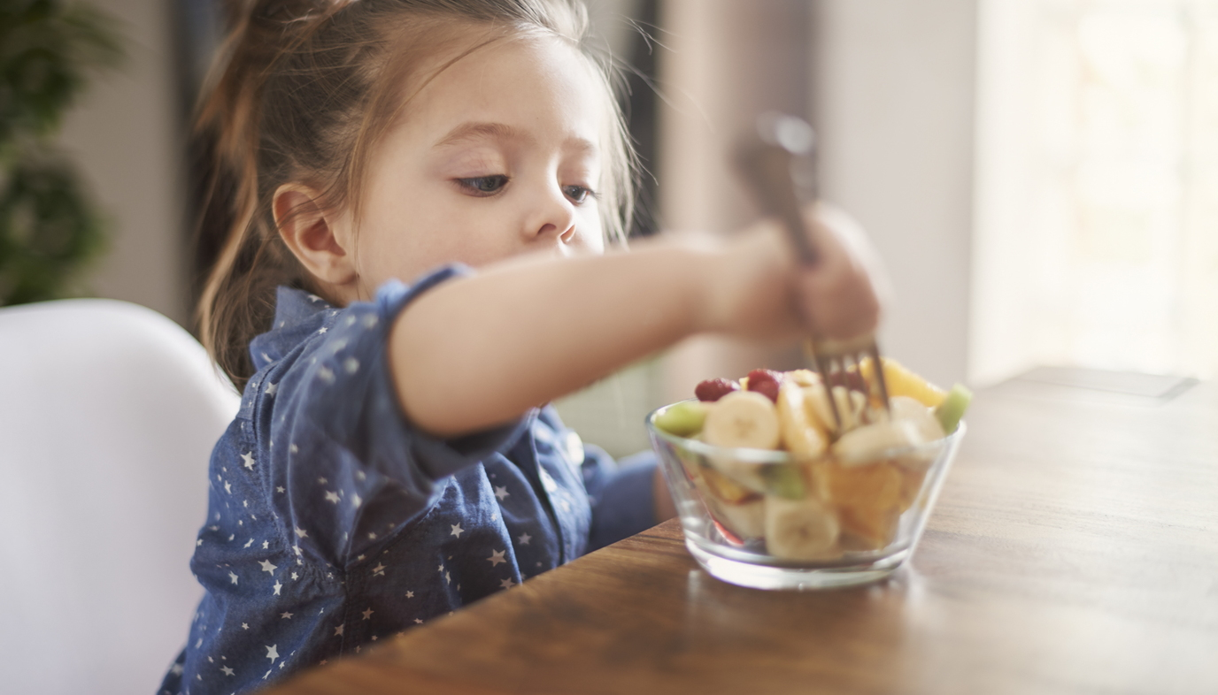 girl eating a bowl of fruit