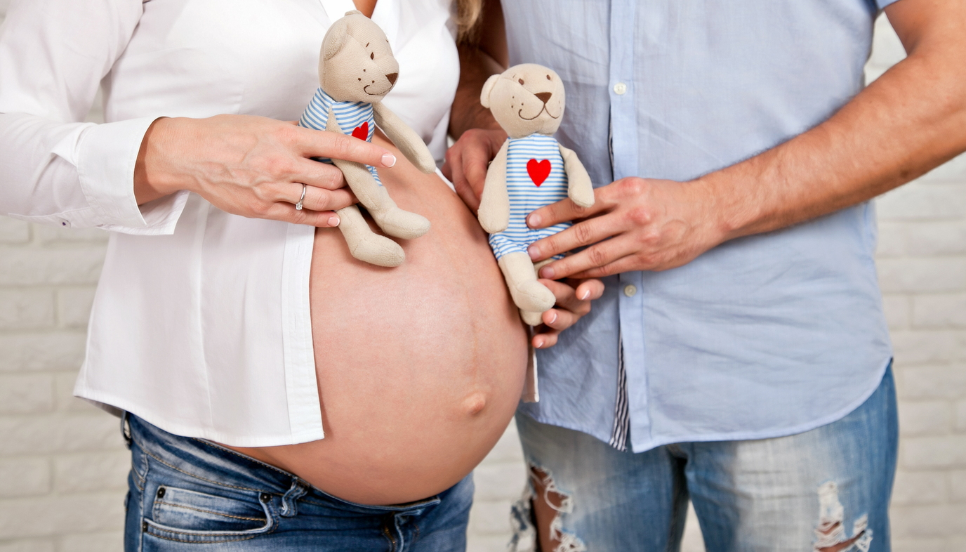 pregnant mom and husband holding two teddy bears
