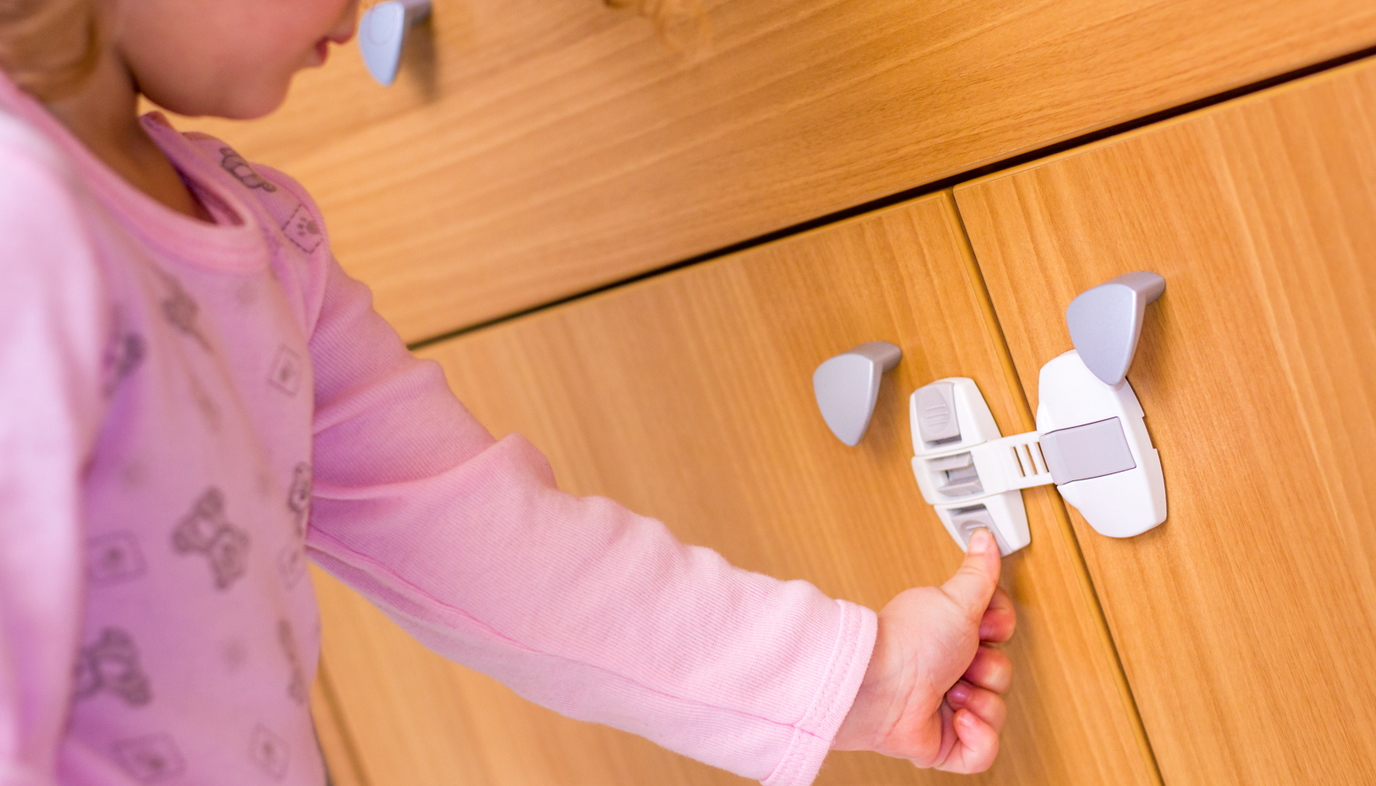 child trying to open childproof cabinet