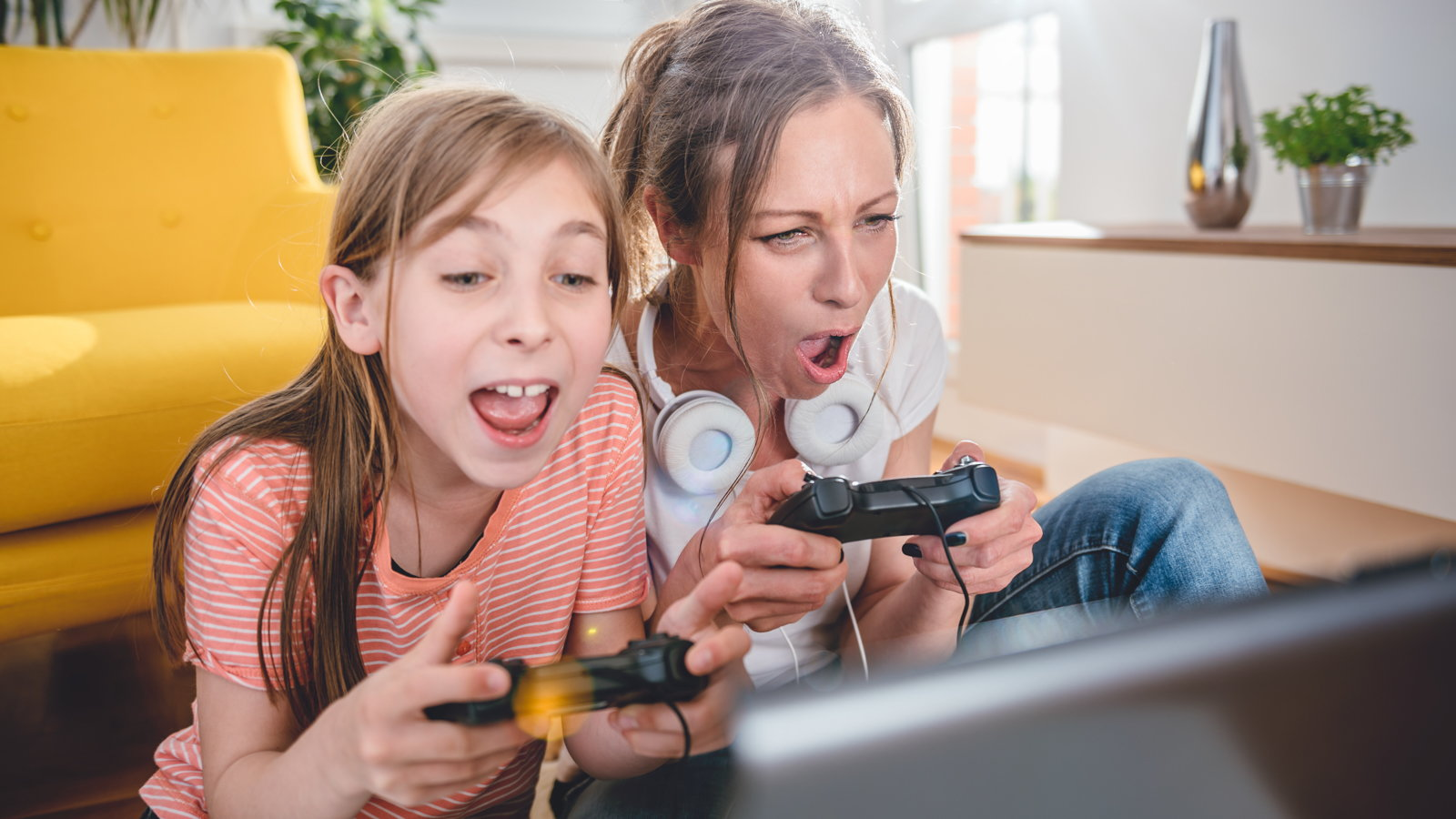 mom playing video game with daughter