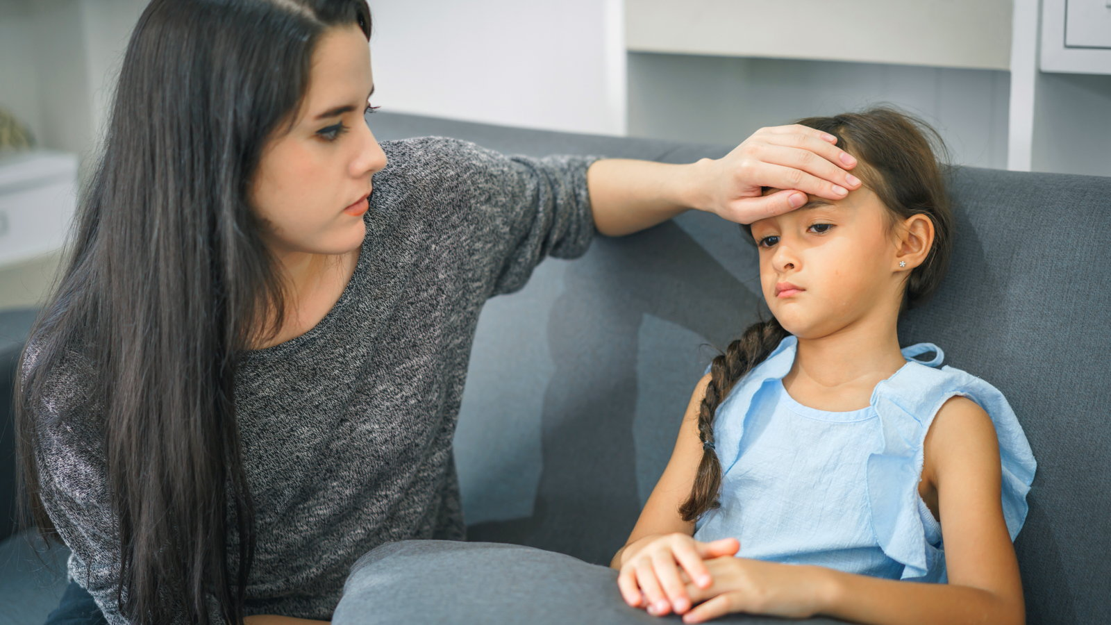 mom feeling sick child's forehead for fever