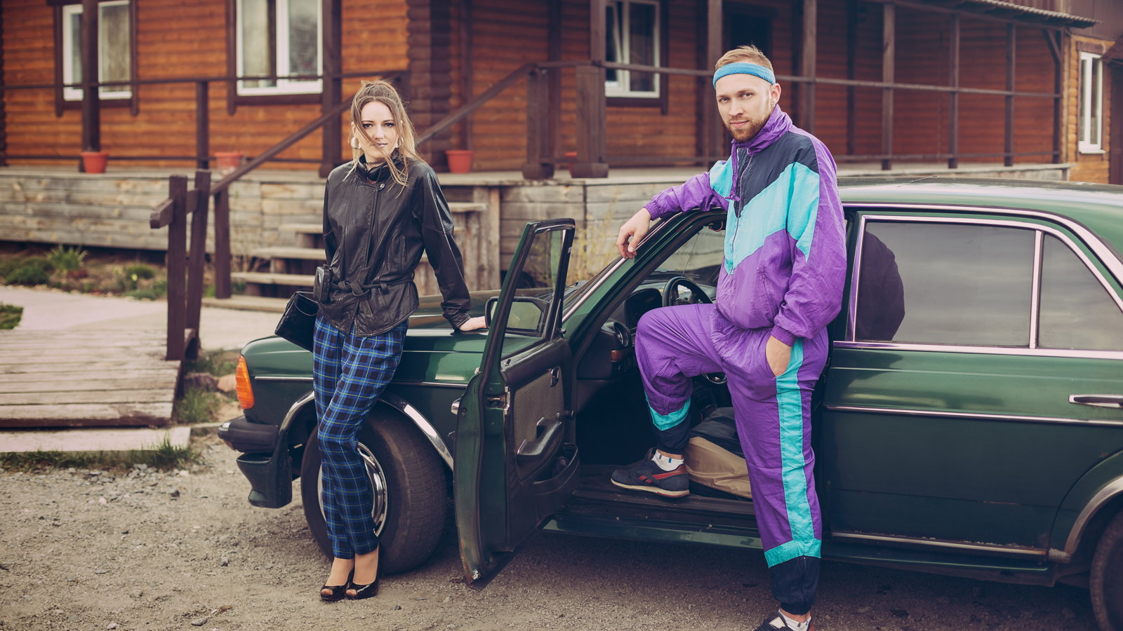 couple wearing 90s clothes with car
