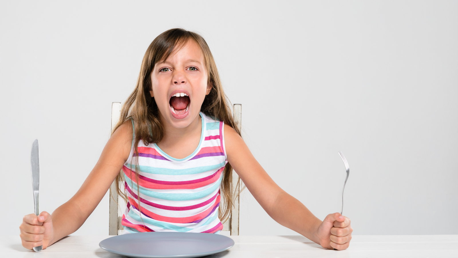 girl screaming for food at dinner table