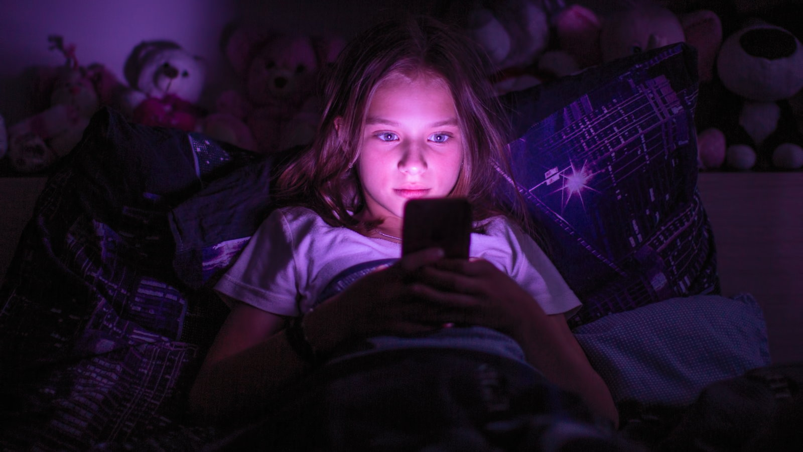 girl using smartphone in bed
