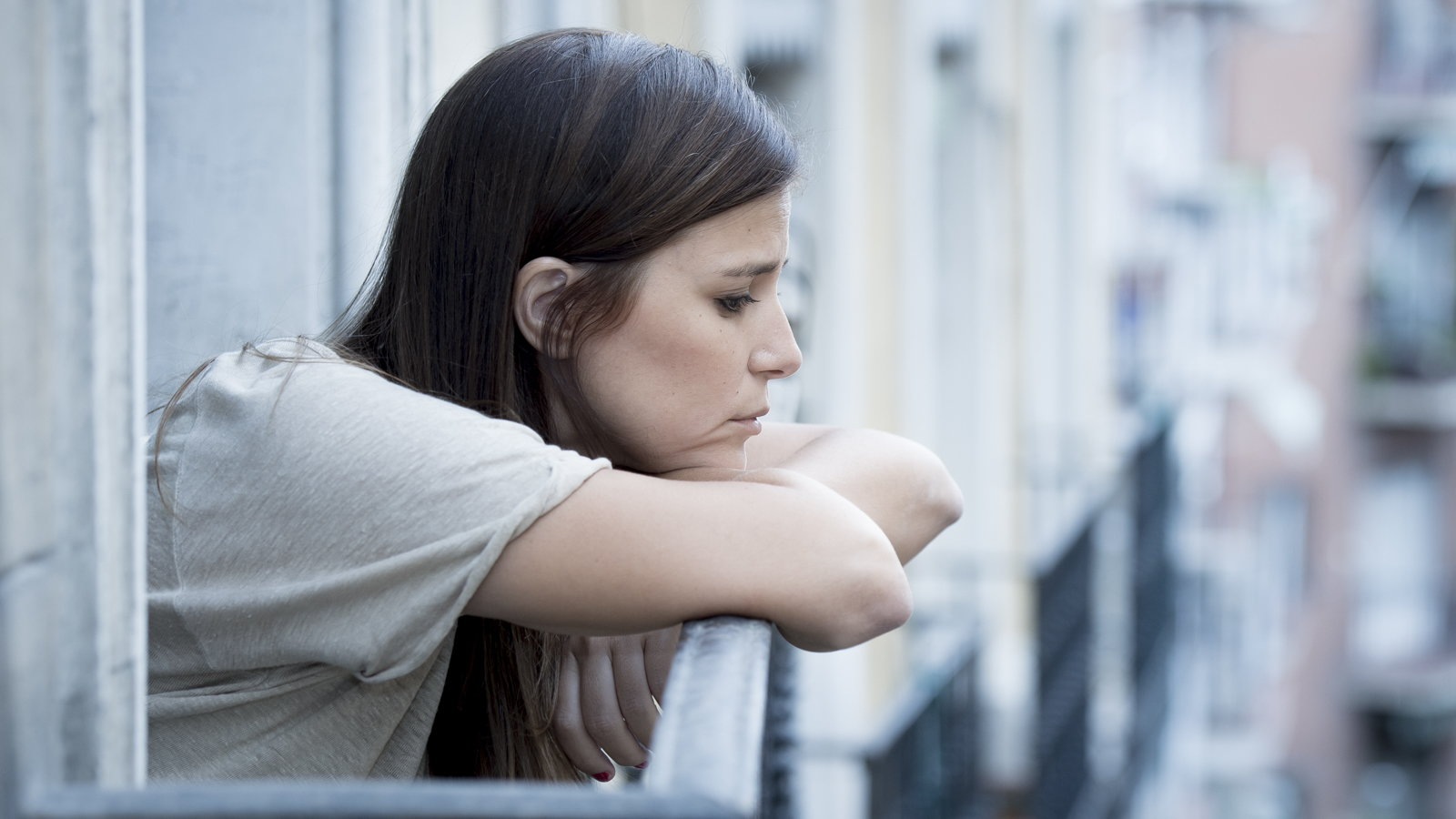 sad woman looking out from balcony