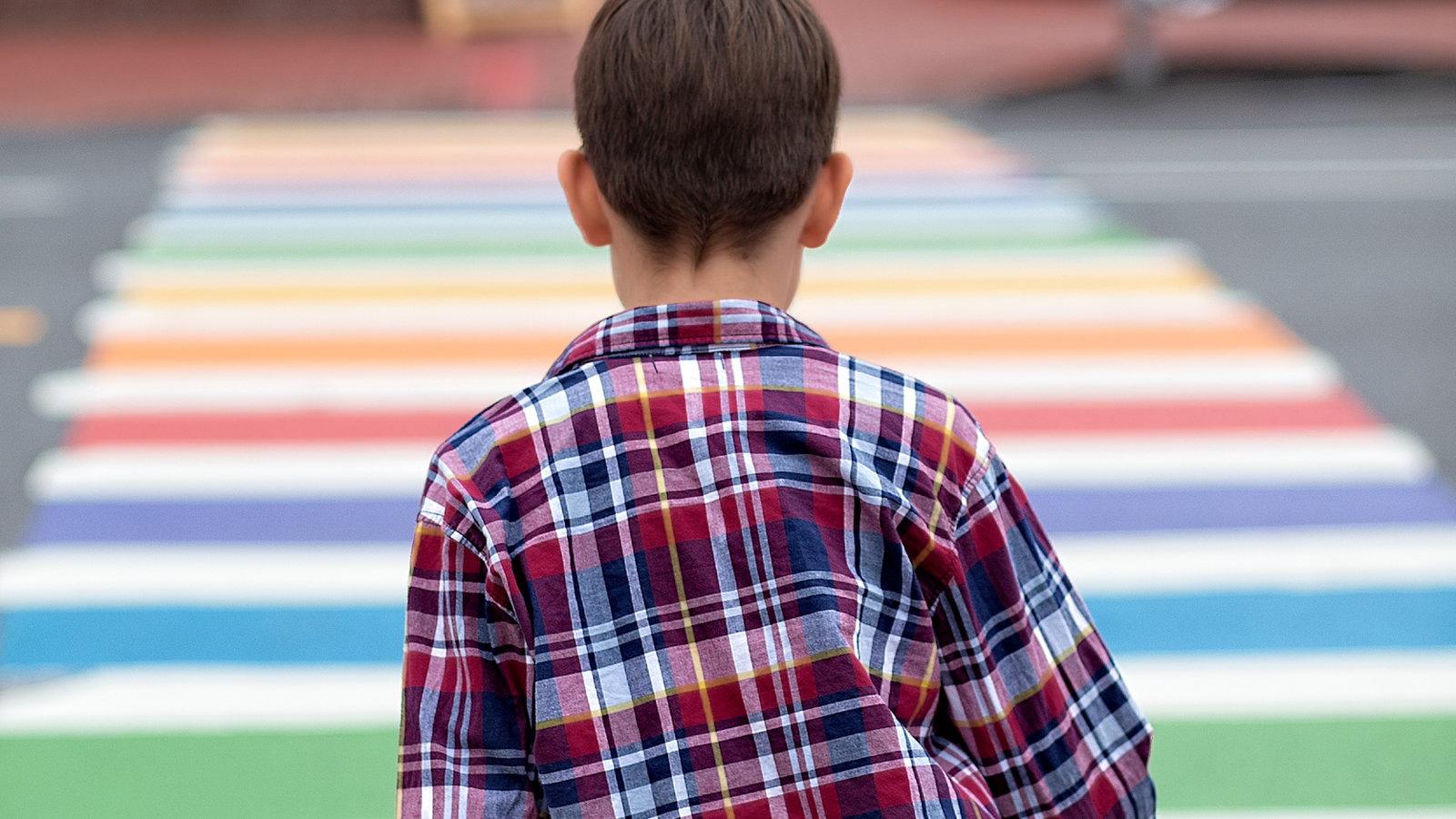 boy walking across colored rug