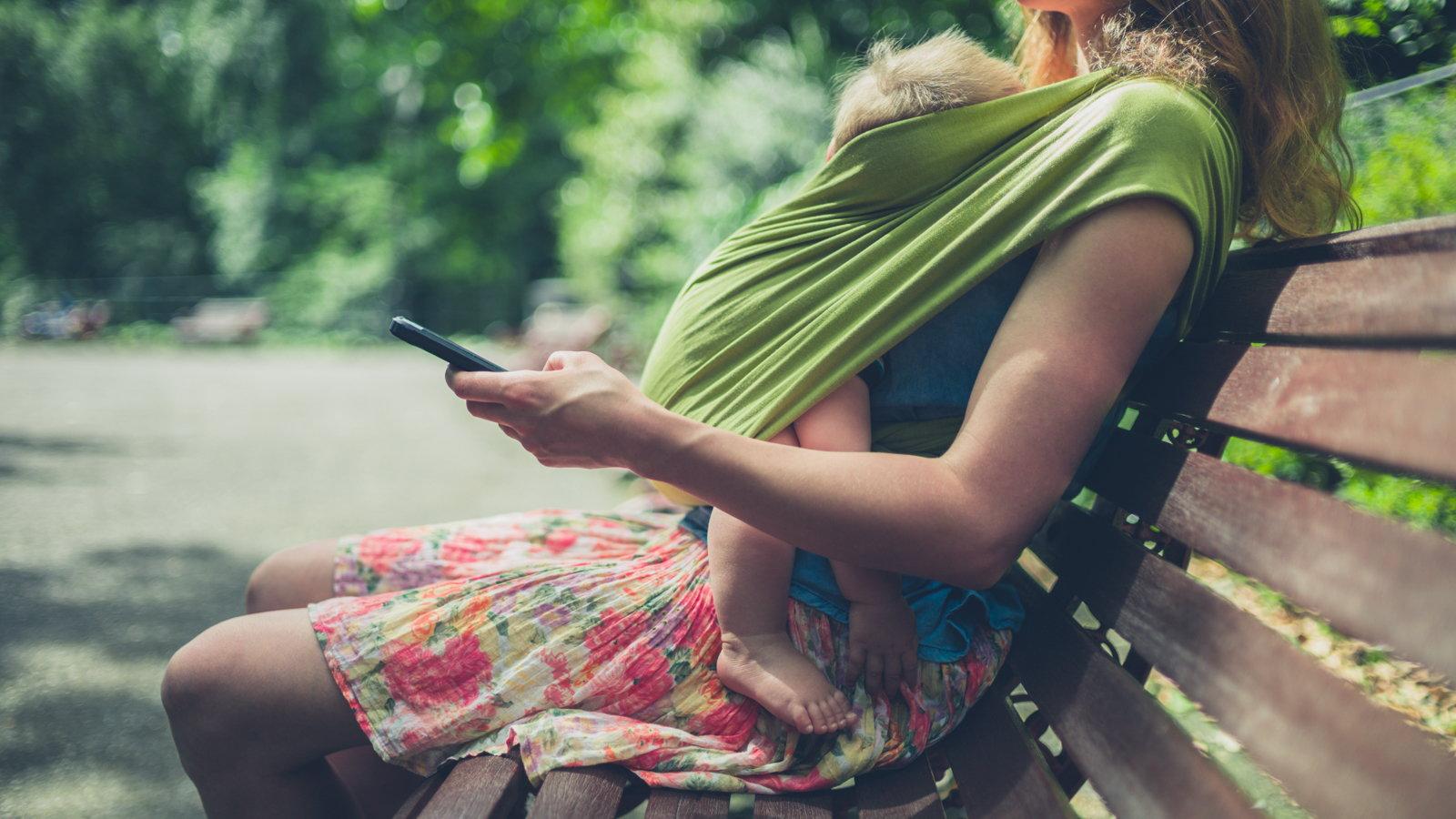 babywearing mom at park using phone