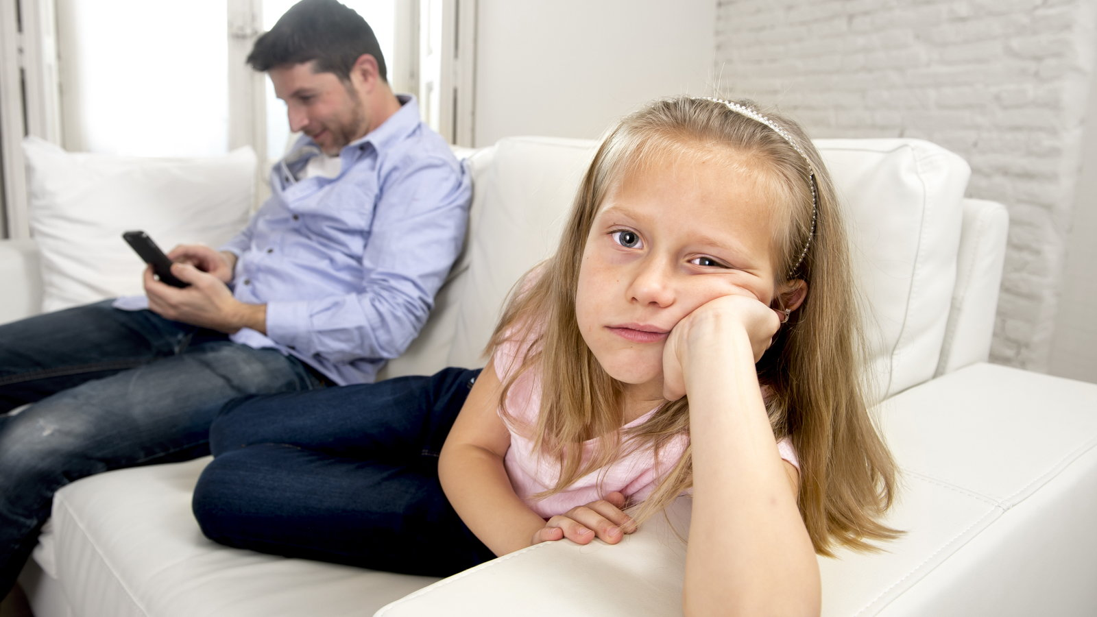 girl being ignored while dad plays on smartphone