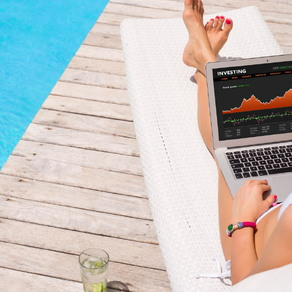 woman on vacation looking at investments on laptop
