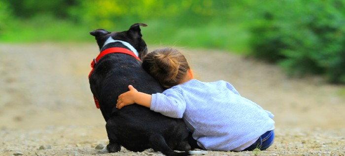 child hugging a dog