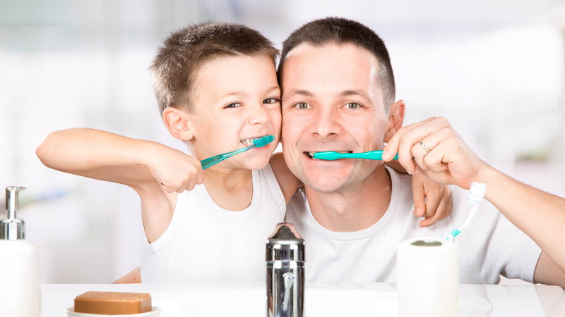 dad and child brushing teeth