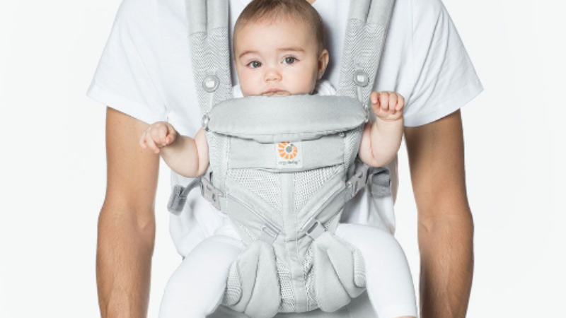 Dad babywearing in a soft structured Ergo carrier.