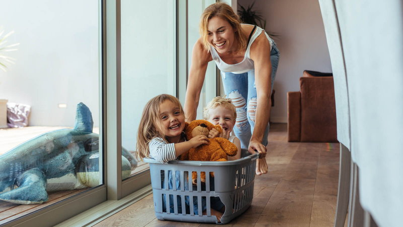 mom pushing kids around in laundry basket