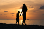 parent walking on the beach with two children
