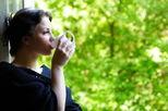 woman sitting in veranda drinking tea