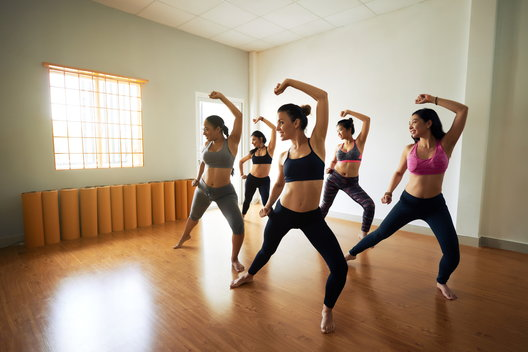 A group of woman exercise together in a group dance class during their addiction recovery.