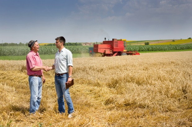 two men shaking hands amidst vast farm land