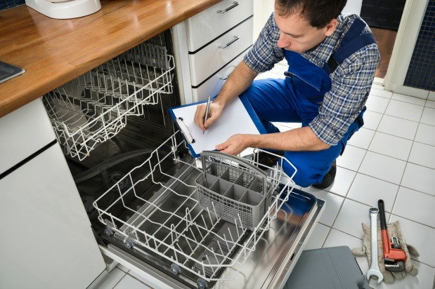 man checking the inside of dish washing machine
