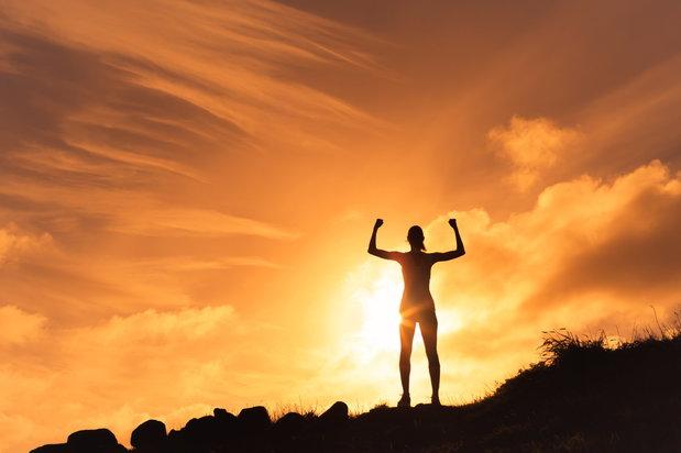 person flexing atop a mountain