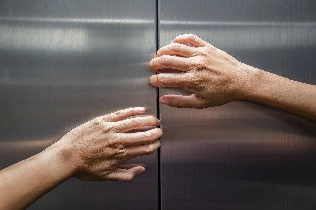 person prying elevator doors open