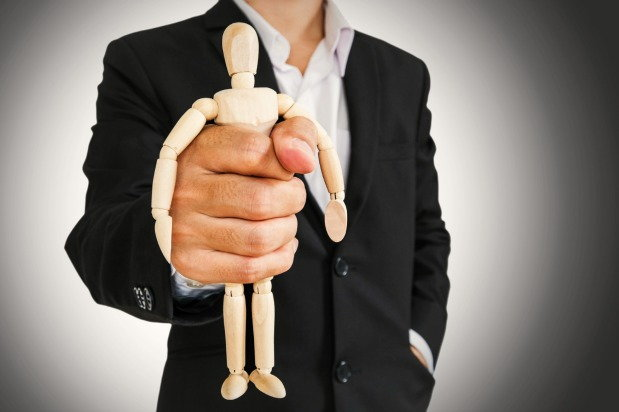Man holding wooden figure