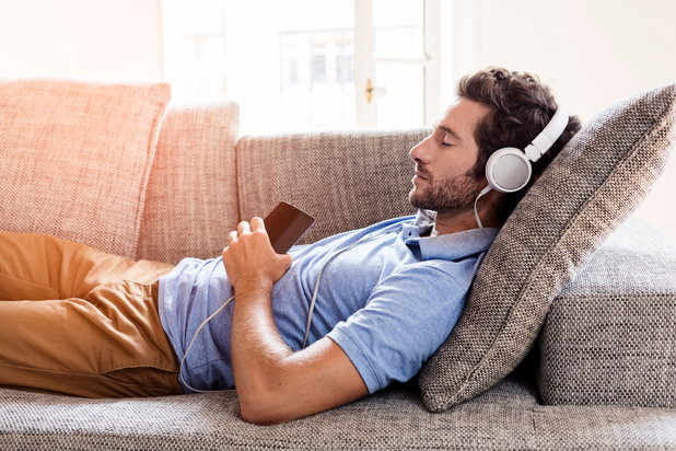 Man relaxing with music to calm his nerves during recovery.