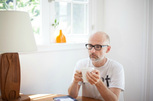 moby sitting at a table drinking tea