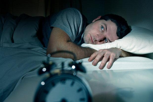 man lying awake on his bed