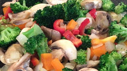 Stir fry with veggies and chicken being cooked.