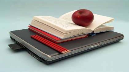A laptop with a book, an apple and pencils on top of it.