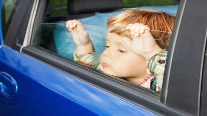 A young boy sadly looks out of a car window.