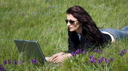 A woman working on her laptop in the grass.