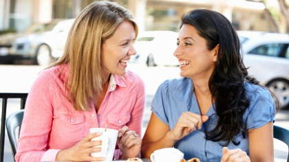 Two women conversing at a coffee shop.