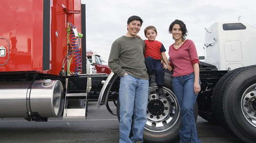 Family standing next to red truck