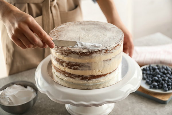 A baker frosting a wedding cake.