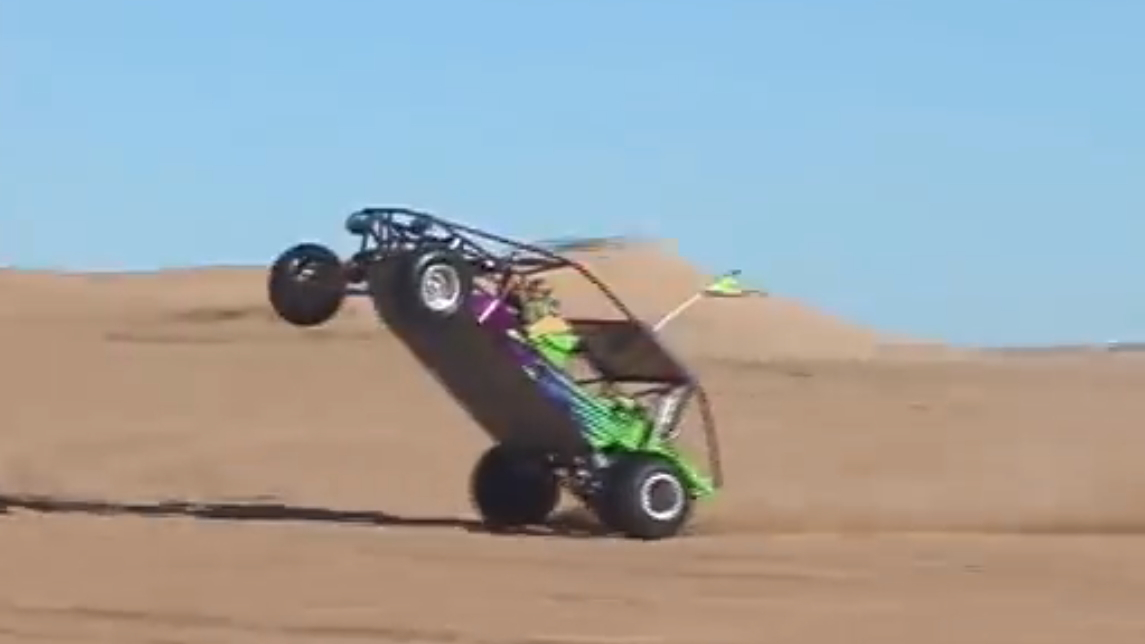 Little kid does a monster wheelie in a sand rail at glamis.